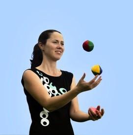 Young woman juggler is juggling balls.